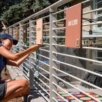 "Artist Angie Eng installs plaques from her outdoor exhibit ""Right on!"" on the railing outside of the Museum of Boulder, at 2205 Broadway, in Sept. 2020. (Don Murray/ Courtesy photo)"