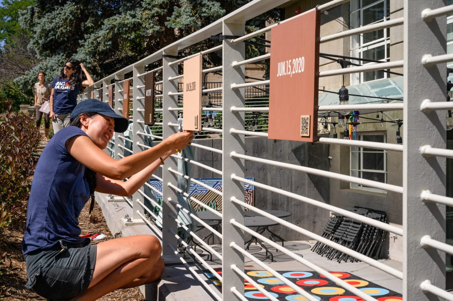 """Artist Angie Eng installs plaques from her outdoor exhibit """"Right on!"""" on the railing outside of the Museum of Boulder, at 2205 Broadway, in Sept. 2020. (Don Murray/ Courtesy photo)"""