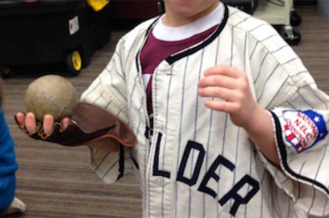 boy in baseball jersey holding ball