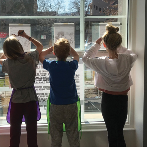 kids tracing art on a window