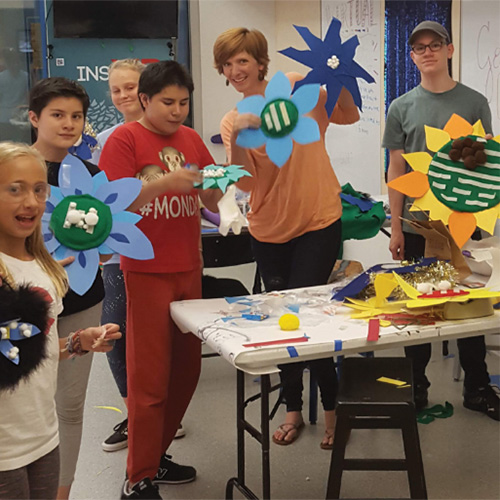 kids showing off artwork in a classroom